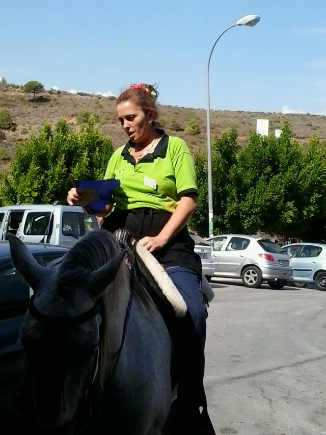 A woman on a horse with a fan (the woman,not the horse)